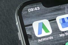 谷歌Adwords在苹果计算机iPhone x屏幕特写镜头的应用象 谷歌广告措辞象 谷歌AdWords应用 束起通信有概念的交谈媒体人社交 库存图片