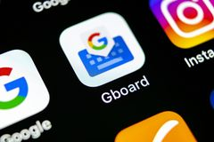谷歌Gboard在苹果计算机iPhone x智能手机屏幕特写镜头的应用象 谷歌gboard app象 3d网络照片回报了社交 束起通信有概念的交谈媒体人社交 免版税图库摄影