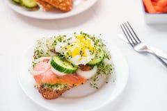 谷物小圆面包用鸡蛋本尼迪克特,熏制鲑鱼,发芽微绿色、葱和黄瓜切片,在服务的白色木头的乳脂干酪 库存图片