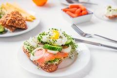 谷物小圆面包用鸡蛋本尼迪克特,熏制鲑鱼,发芽微绿色、葱和黄瓜切片,在服务的白色木头的乳脂干酪 图库摄影