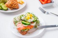 谷物小圆面包用鸡蛋本尼迪克特,熏制鲑鱼,发芽微绿色、葱和黄瓜切片,在服务的白色木头的乳脂干酪 库存照片