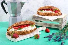 谷物新月形面包用乳脂干酪和新鲜的草莓 有用的早餐 库存图片