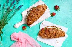 谷物新月形面包用乳脂干酪和新鲜的草莓 有用的早餐 免版税库存图片