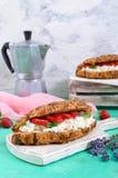 谷物新月形面包用乳脂干酪和新鲜的草莓 有用的早餐 免版税库存照片