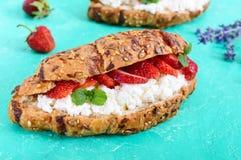 谷物新月形面包用乳脂干酪和新鲜的草莓 免版税库存图片