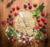 谷物燕麦与匙子和新鲜的可口莓果的剥落堆在木背景 库存照片