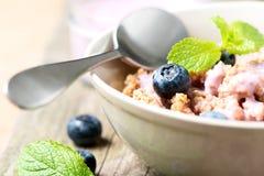 谷物用酸奶和新蓝莓匙子关闭 免版税库存图片