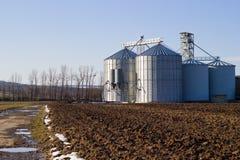 谷物的筒仓在一个被犁的域 免版税库存图片