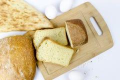 谷物面包店不同形式的分类顶视图:面包,新月形面包,在白色隔绝的小圆面包woodden背景 免版税库存照片