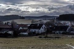 谷的一个小结冰的村庄在草甸和领域之间 库存照片
