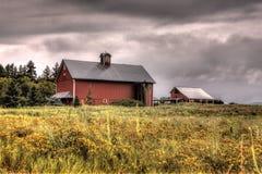 谷仓在风雨如磐的天空下。 免版税库存图片