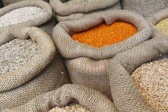 豆、米、扁豆、燕麦、麦子和大麦在黄麻大袋 免版税库存照片