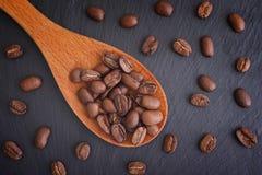豆关闭咖啡木的图象匙子 免版税库存图片