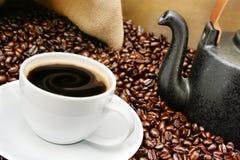 豆关闭在烤的咖啡杯  免版税图库摄影