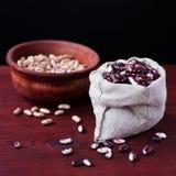 豆在布料袋子和在木碗 免版税图库摄影