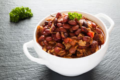 豆用猪肉在辣西红柿酱炖了用葱、辣椒粉、啤酒、响铃和桃红色胡椒 库存照片