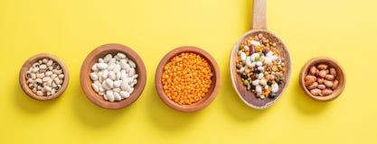 豆类的分类在木碗的在黄色,背景,被隔绝的,顶视图,横幅 图库摄影