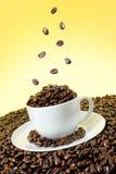 豆落在白色的咖啡杯 库存照片