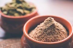 豆蔻果实粉末或elaichi粉末在碗在喜怒无常的背景用荚 图库摄影