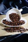 豆被倒置的咖啡杯 免版税库存图片