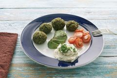 豌豆、菠菜、蓬蒿、奎奴亚藜、燕麦和鸡蛋素食丸子在蕃茄和鲕梨陪同的葡萄酒蓝色木头 免版税库存图片