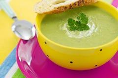 豌豆奶油色汤用荷兰芹和油煎方型小面包片,在桃红色牌照 免版税库存图片