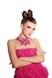 象一个玩偶的女孩在桃红色礼服 免版税库存图片