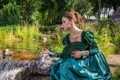 象一位公主的一名妇女葡萄酒礼服的在神仙的公园 库存照片