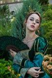 象一位公主的一名妇女葡萄酒礼服的在神仙的公园 图库摄影