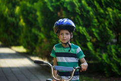 画象一辆自行车的孩子男孩在柏油路在公园 免版税库存图片