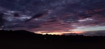 象五颜六色的天空、黑山和有风气候的晚上 库存图片