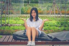 画象亚裔妇女坐黑枕头和木大阳台在庭院里,微笑和握开放手斜向一边 免版税库存图片