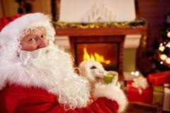 画象享用的圣诞老人喝茶为圣诞节假日 免版税图库摄影