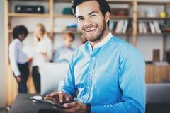 画象使用片剂的成功的确信的西班牙商人在手上和微笑对照相机在现代办公室 免版税库存图片