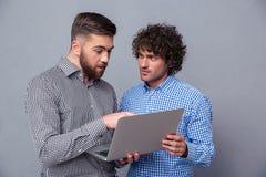画象使用膝上型计算机的两个人 免版税库存图片