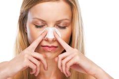 画象十几岁的女孩申请清理在鼻子的小条 库存图片