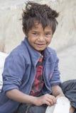 画象叫化子男孩为从一个路人的金钱乞求在Leh Ladakh,印度 库存图片