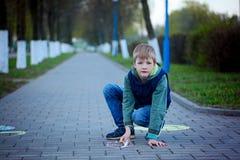 画象在沥青的男孩图画在春天公园 免版税库存照片