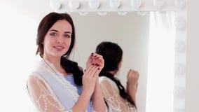 画象女孩用穿着考究的手,用途手奶油,接触她在面颊的夫人软和至善至美的皮肤, 影视素材