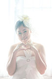 画象女性新娘用塑造在窗口白色背景的手心脏标志 图库摄影