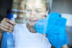 画象妇女清洁窗口在家 免版税库存图片
