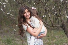画象妈妈和女儿是拥抱和微笑户外,家庭,母性,孩子 图库摄影