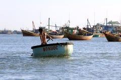 象小圆舟的圆的渔船的年轻越南男孩 库存照片