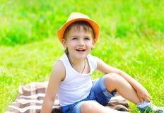 画象帽子的小男孩孩子坐草在夏天 免版税库存照片