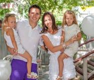 画象幼小四口之家在与白色的咖啡馆 免版税库存图片