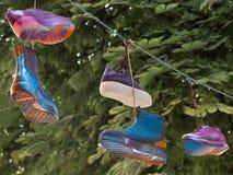 象征性地显示的文化多元化 垂悬在绳子的鞋类 库存图片