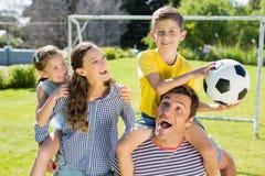 画象微笑做父母运载他们的他们的肩膀的两个孩子 免版税库存图片