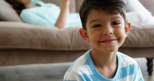 画象微笑的男孩坐地毯在客厅 股票录像