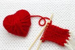 象心脏的红色毛线球在白色钩针编织背景 浪漫情人节概念 红色心脏由与plac的毛纱制成 库存照片
