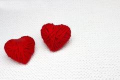 象心脏的红色毛线球在白色钩针编织背景 浪漫情人节概念 红色心脏由与plac的毛纱制成 免版税库存照片